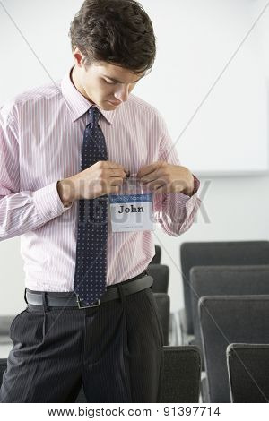 Male Delegate Attaching Name Badge At Conference