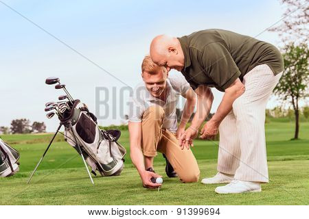 Two men putting ball on tee at course