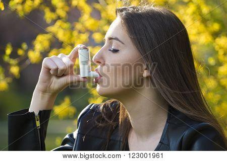 Teenager girl using asthma inhaler in park