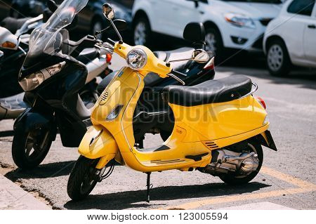 Seville, Spain - June 24, 2015: Yellow Piaggio Vespa vintage sprint motor scooter motorbike motorcycle parked in city.