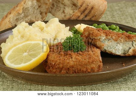 two fresh cod fishcakes with mashed potato and peas