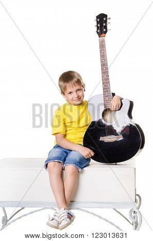 Boy Sitting And Holding The Guitar In Vertical Position Isolated On White Background