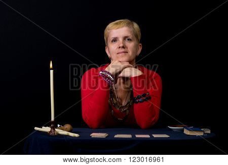 Portrait of woman - soothsayer sitting at the table with candle and playing cards