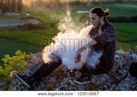 Handsome young man sitting on a rocks and smoking electronic cigarette at outdoors.