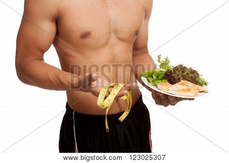 Muscular Asian Man Diet With Clean Food And Measuring Tape