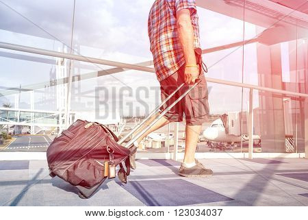 Traveler man at international airport moving to terminal gate for airplane travel - Wanderlust concept with solo person on the go - Rose quartz filter halo with focus on leg and blurred motion on bag