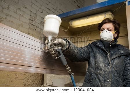 Saint-Petersburg, Russia - March 17, 2016: Carpenter painter paints the furniture board with a spray gun on the production line small wholesale furniture factory on the background of the air intake.
