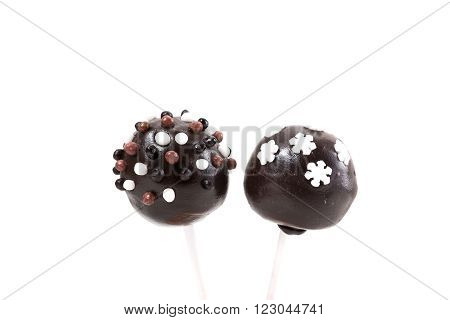 Two chocolate cakepops with decoration on isolated background