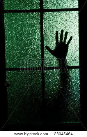 Blurred silhouette of a hand behind a window or glass door (symbolizing horror or fear)