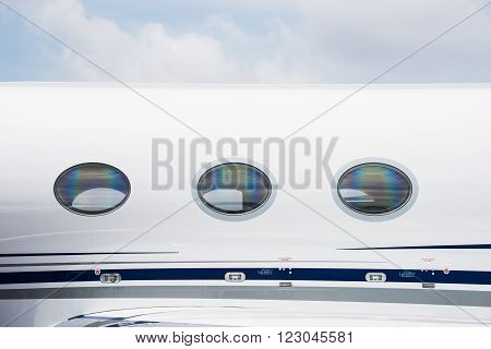 Windows and fuselage detail of white business jet aircraft.