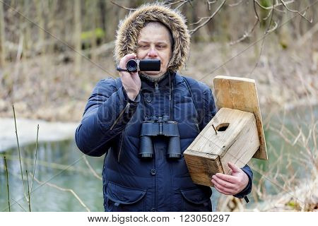 Ornithologist with camcorder and bird cage near river