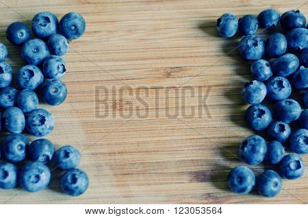 Blueberries against a worn wooden background (shallow DOF selective focus) with copy space for your text retro style