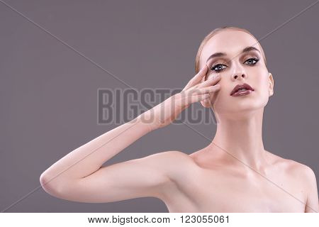 The white girl on a gray background showing the beauty of makeup