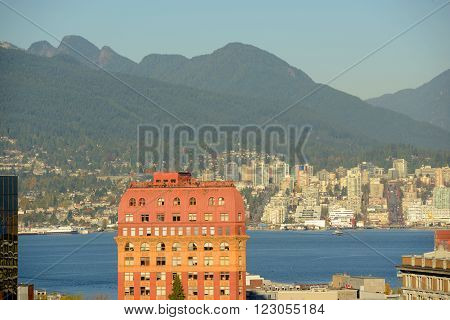 Historic Second Empire style Dominion Building and North Vancouver city skyline across Vancouver Harbour, Vancouver, British Columbia, Canada.