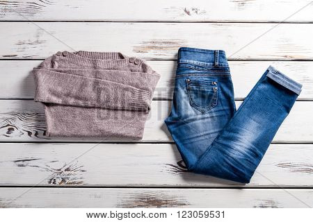 Bateau neckline sweater and jeans. Jeans and sweater on shelf. Blue jeans and beige sweater. Lady's clothes for cool weather.