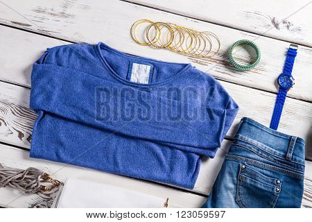 Female sweatshirt with blue jeans. Clothes and accessories on table. Tiny bracelets and spring clothes. Casual garments in clothes shop.