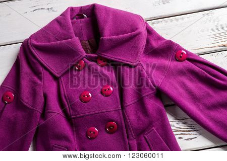Woman's fashionable purple coat. Purple coat on wooden background. Colorful coat from new collection. Bright stylish coat for spring.