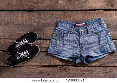 Denim shorts and black keds. Shorts and shoes on table. Simple clothing on old shelf. Classic clothes on aged floor. poster