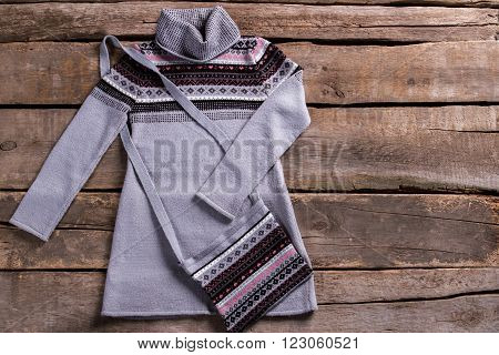 Warm gray tunic with purse. Warm tunic on old floor. Gray tunic on brown shelf. Lady's garment on aged table.