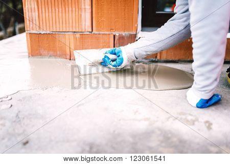 industrial worker waterproofing part of house exposed to rain