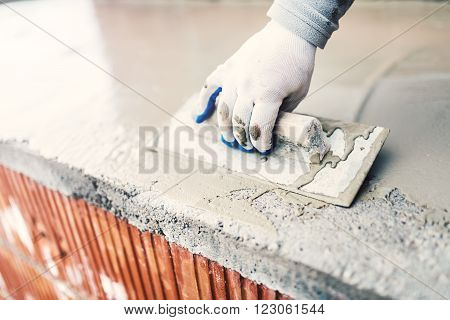 protective material against water on house building. worker waterproofing cement