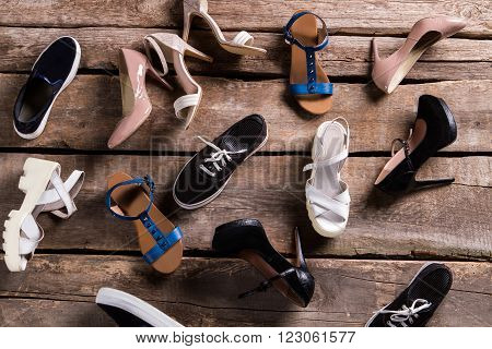 Different female shoes on floor. Footwear on old wooden background. Shoes on retro boutique shelf. Mess on shoe store's floor.