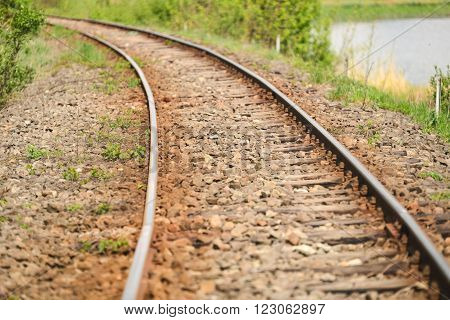 detail of an old railway that runs along a lake in the country