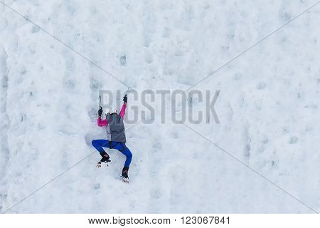Person child climbs up the icy rock. Child climbing frozen waterfall