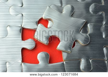 Close up incomplete silver puzzle on the red paper