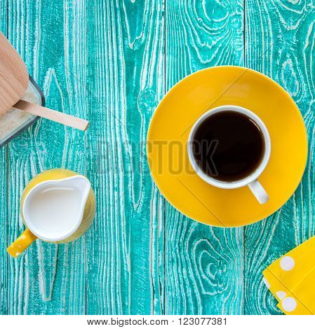 cup of black tea on yellow plate and yellow milk jug and sugar-bowl