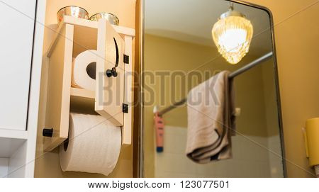 Wooden toilet paper holder with small door, crescent moon cut into door, toilet paper inside and one roll on spool.  Essential paper needs in bathroom.   Low angle partial view of bathroom, mirrored light, towel on a shower curtain bar.