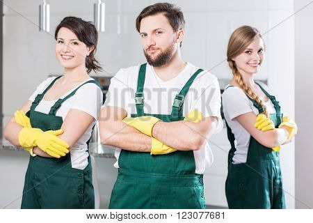 Three young people in cleaning uniforms standing together