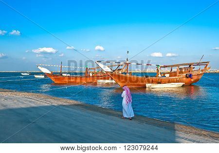 Dammam, Saudi Arabia - November 16, 2008: A local man walking in front of the Dow boats in the fisherman area.