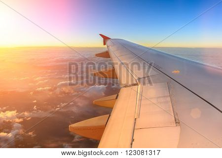 Aerial view of airplane flying above shade clouds and sky from an airplane fly during the sunset. View from the plane window of emotional moment during international travel around the world.