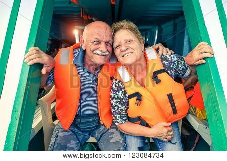 Senior couple with life jacket traveling on tropical boat excursion - Active elderly tourists having fun ready to sail - Happy retired friends on island tour - Concept of travel and joyful retirement