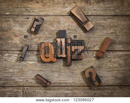 quiz, single word set with vintage letterpress printing blocks on rustic wooden background, surrounded by exclamation and question marks