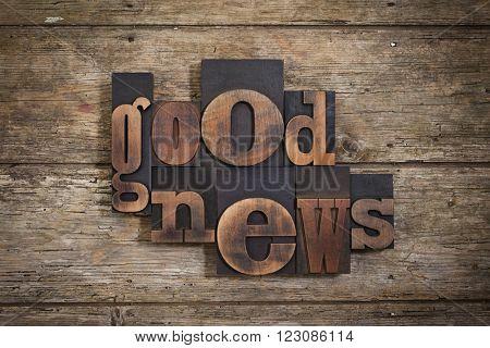 good news, phrase set with vintage letterpress printing blocks on rustic wooden background