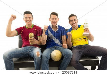 Three friends sitting on sofa wearing sports shirts smiling interacting with camera holding trophy and ball, white background.