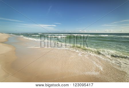 Wide angle view of sparkling waves and surf on a Florida beach on a sunny day