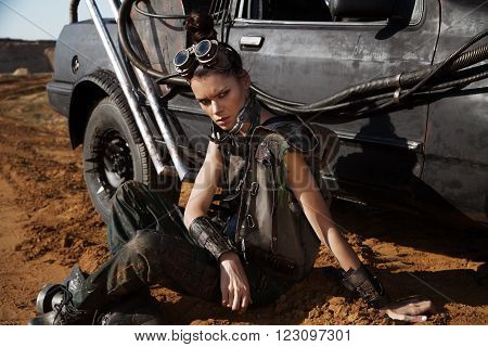 Young woman warrior in brutal futuristic style clothes with car