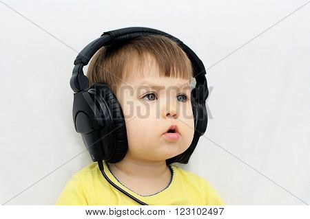 Little baby girl listening music with headphones and singing song