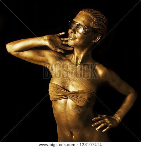 Lovely young woman in gold with sunglasses.