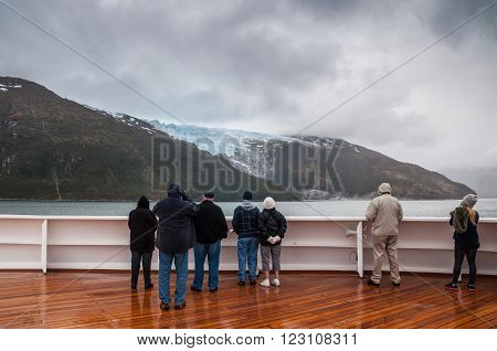 Glacier Alley, Beagle Channel, Chile - December 10, 2012: Passengers on board the cruise ship Veendam viewing beautiful Romanche Glacier on Glacier Alley. Taken on a overcast rainy day. Glacier alley is also of historical importance as it was described in