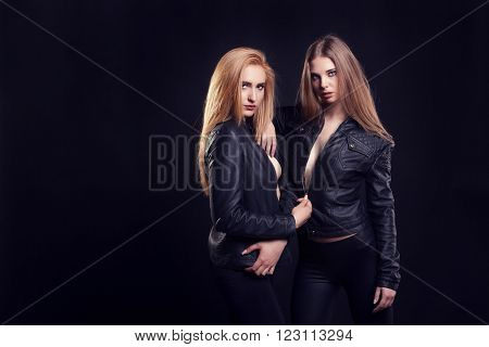 Two Hot Women In Leather Jacket On Black Background