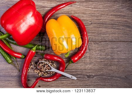 Sweet And Spicy Pepper On Wooden Background