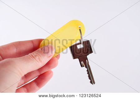 Hand holding metal key hanging on a yellow keyring