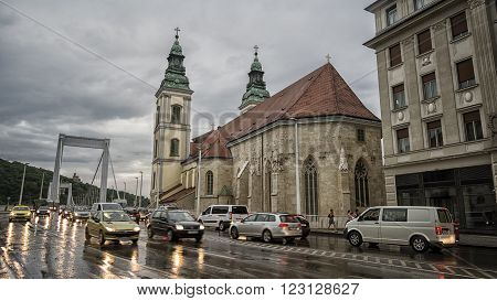 BUDAPEST, HUNGARY, JULY 8, 2015: Slow traffic on a rainy day at Budapest, Inner City Parish Church can be seen, Erzsebet Bridge on the background.