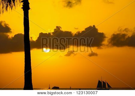KEY WEST, USA - MAY 10, 2015: The sun going down above the Key West Bight on the luminous orange sky with some clouds and silhouettes of a sailing ship and a palm tree.