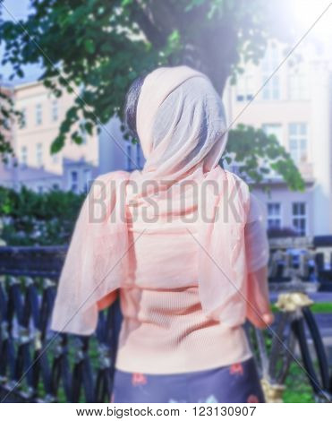 Nice woman stranger in pink scarf turned back at sunny day