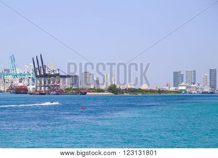 MIAMI BEACH, USA - MAY 9, 2015: The Port of Miami with big containerships cruise liners and a jet ski in front skyline in the back.